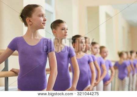 Happy Young Ballerina At Dance Lesson. Group Of Young Ballet Girls Standing In Row At Ballet Barre D