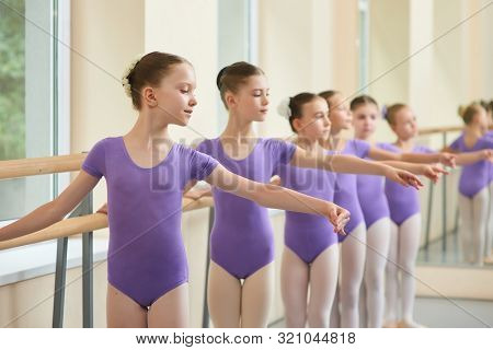 Young Ballerinas In Choreography Class Of Ballet School. Group Of Cute Ballet Performers Doing Balle