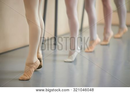 Little Ballerina Legs In Pointe Shoes. Dancers Legs On Pointe Near The Choreographic Training Machin