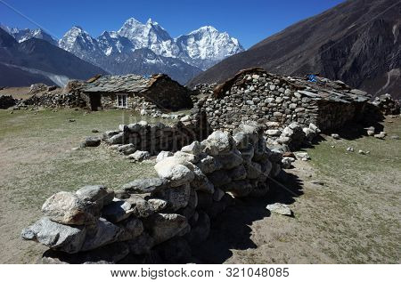 Old stone houses in Dusa village (4530 m) along the Everest trek, View of Kangtega (6685 m) and Thamserku (6608 m) in Himalayas mountains in the end of may, Sagarmatha national park, Solukhumbu, Nepal