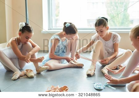 Young Ballerinas Tying Pointe Shoes. Four Beautiful Ballet Dancers In Dresses Sitting On The Floor A