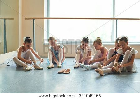 Young Ballerinas Putting On Shoes In Studio. Six Young Ballet Dancers Sitting On The Floor In Differ