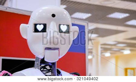 White Cute Humanoid Robot With Heart Shape Eyes At Technology Exhibition. Future, Emotion, Ai And Ro
