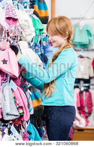 Smiling cute girl looking at woolly hat in the shop
