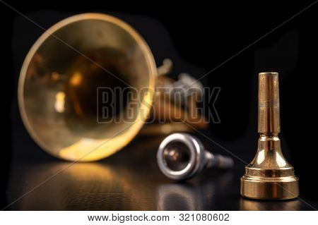 Mouthpiece And Trumpet Covered With Patina On A Dark Table. Accessories For Musicians Ready To Use.