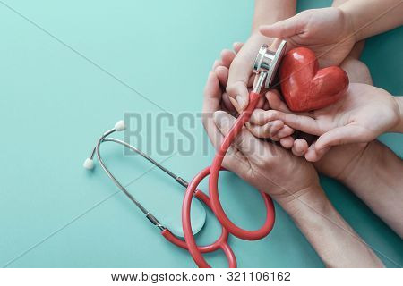 Family Hands Holding Red Heart With Stethoscope, Heart Health,  Health Insurance Concept, World Hear