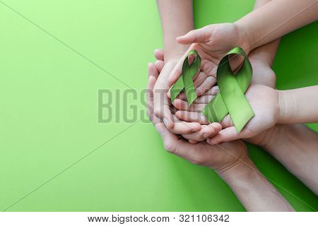 Adult And Child Hands Holding Lime Green Ribbon On Green Background, Mental Health Awareness And Lym