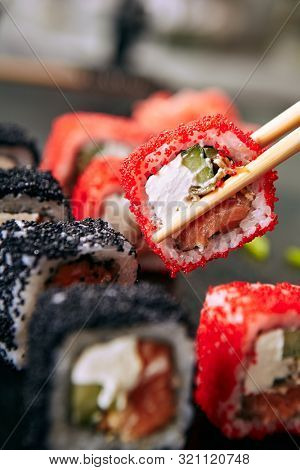 Chopstick holding maki sushi roll with rice, cream cheese, salmon, eel, cucumber, flying fish caviar. Nori maki rolls with raw trout, red and black tobiko on natural dark stone background close up