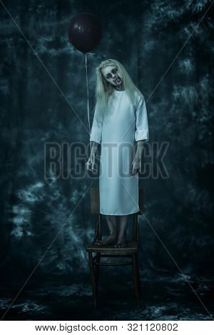 A full length portrait of a scary pale girl from a horror film with a baloon on the chair. Zombie, halloween.