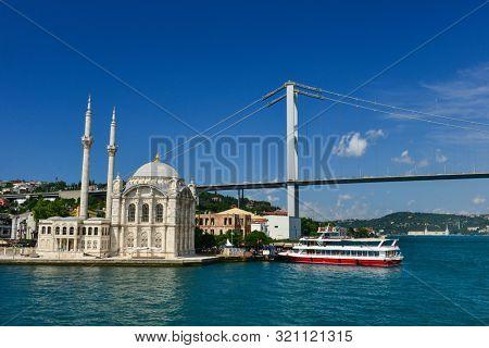Ortakoy Mosque and a passenger boat boarding Ortakoy Wharf - Istanbul, Turkey
