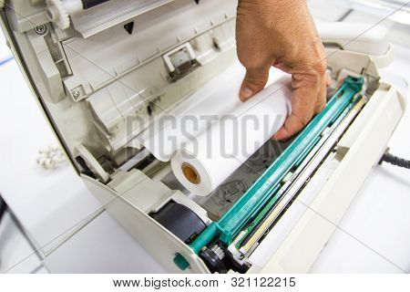 Hand of Man hold Fax paper setup to fax machine poster