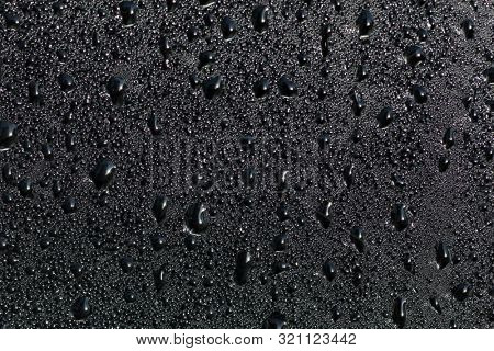 Drops of black liquid on a glass surface
