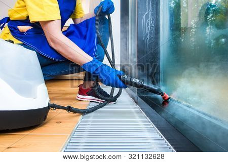 Professional Cleaning Service. Woman In Uniform And Gloves Sponge Washes Panoramic Windows In The Co