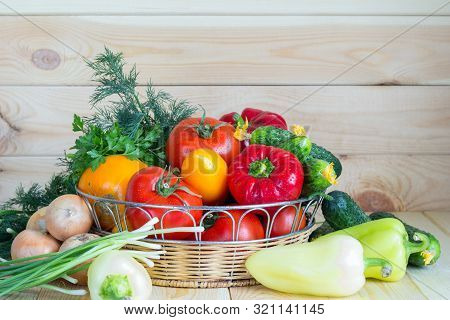 Fresh Organic Vegetables In Wicker Basket On Wooden Table With Copy Space. Summer Harvest Concept.