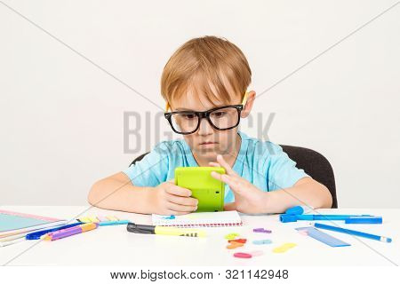 Little Student Boy Counts Something With Calculator. Child Doing Homework At Home. Preschool Boy Doi