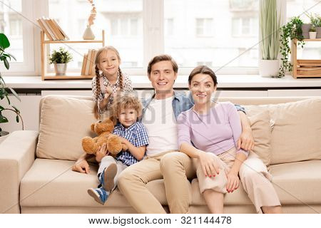 Four family members in casualwear sitting on couch by window, looking at camera and enjoying weekend at home