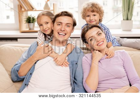 Young cheerful family of father, mother and two cute siblings embracing while relaxing on sofa at home on weekend