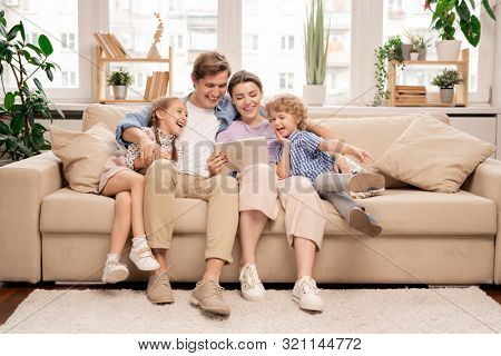 Young joyful casual family of two kids and couple sitting on sofa and watching funny video or cartoons in touchpad
