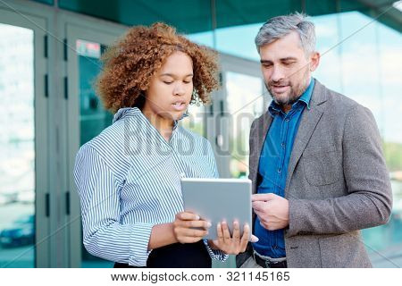 Young intercultural businesswoman and her male colleague looking at online data on tablet display outdoors