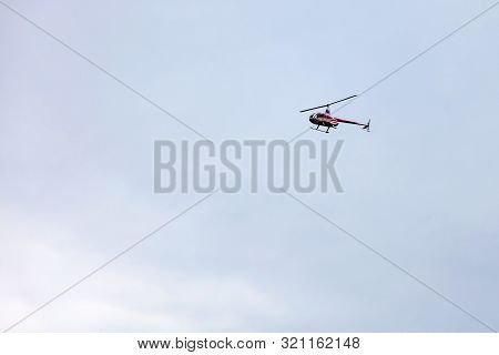 A Red Pleasure Helicopter Flies In The Sky During A Sightseeing Walk Against A Gray Sky. Air Transpo