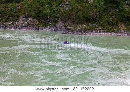 Aerial View Of A Red Rubber Motor Boat Sailing On A Green River In The Mountains Between Rocks And C