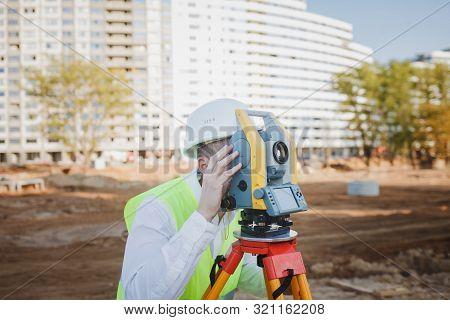 Geodetic Works. Surveyor Engineer In Protective Wear And Helmet Using Geodetic Equipment