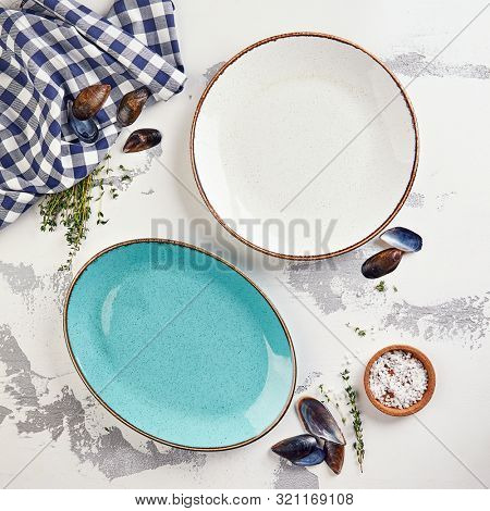 White and turquoise dishes plates on gray plaster table texture, food photography template. Mediterranean seafood cuisine mockup with blank crockery tableware, seashells, herbs and sea salt top view