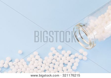Homeopathic Globules And Glass Bottle On Blue Background. Alternative Homeopathy Medicine.