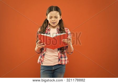 Shes A True Bookworm. Adorable Small Child Reading Book On Orange Background. Cute Little Girl Readi