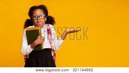 I Dont Know. Puzzled Black School Girl Shrugging Shoulders Holding Books On Yellow Studio Background