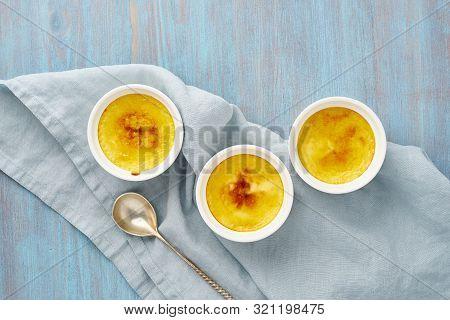 Crema Catalana, Spanish Dessert In Three Ramekin On Blue Table, Copy Space, Top View