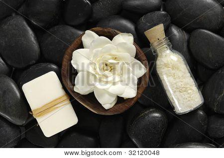 gardenia flower ib wooden bowl with salt in glass on black pebbles