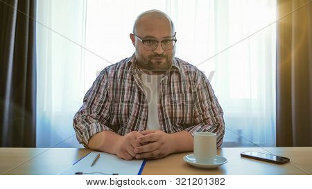 Male Online Teacher Speaks On Laptop Webcam, Fat Man In Glasses Making Videocall Or Webinar Or Job I