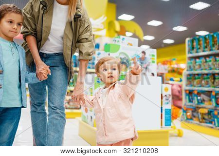 Mother with her little children in kids store