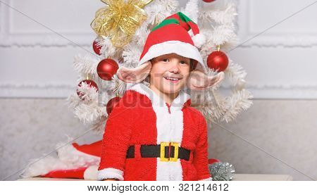 Boy Kid Dressed As Cute Elf Magical Creature White Artificial Ears And Red Hat Near Christmas Tree.