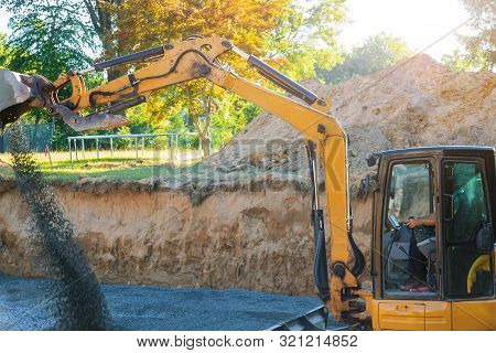 Industrial Construction Site Excavator Moving Gravel And Rocks For Foundation Under Construction Hom