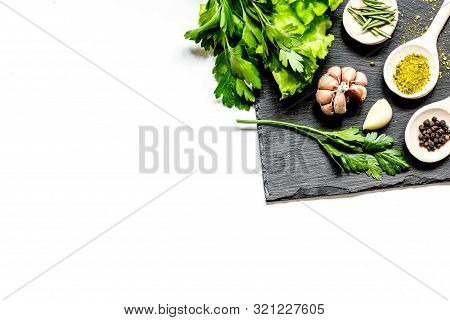 Various Spices In Wooden Spoons On White Background Top View