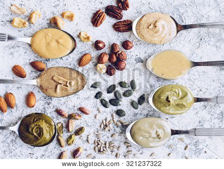 Nuts And Seeds Butter On A Spoons With Ingredients. Homemade Raw Organic Almond, Hazlenut, Cashew, P