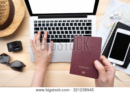 Hand Holding Passport With A Map And Laptop For Planning To Travel.traveling Journey Vacation Holida