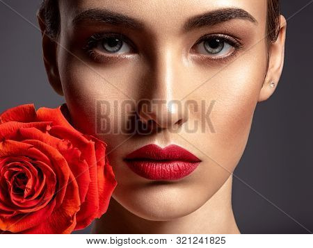 Beautiful young fashion woman with red lipstick. Glamour fashion model with bright gloss make-up  posing at studio. CLoseup beauty portrait with a flower. Red rose.
