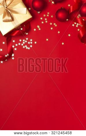 New Year Christmas Golden Presents With Ribbon, Christmas Balls, Gold Confetti Stars On Red Backgrou