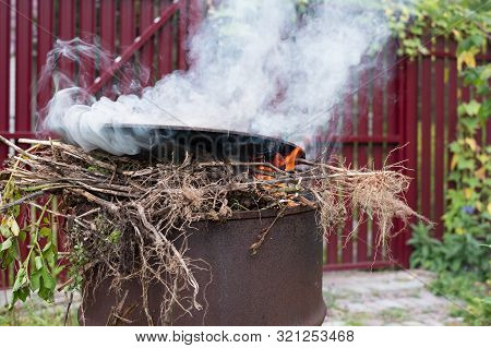 Garden Incinerator Made From A Barrel With Burning Plants And Rubbish