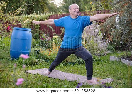 Senior Hsipanic Man Is Working Out In Garden, Standing In Virabhadrasana 2 Or Warrior Pose