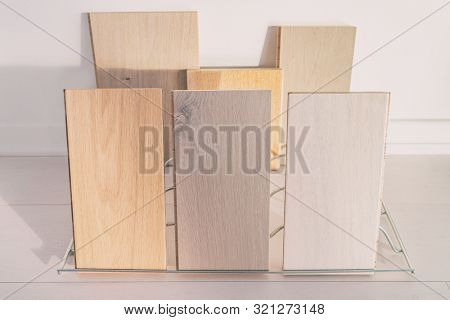 Hardwood floor samples at flooring store. Display of selection of engineered hard wood floors with different tints, grey oak, natural maple for home remodeling condo construction.