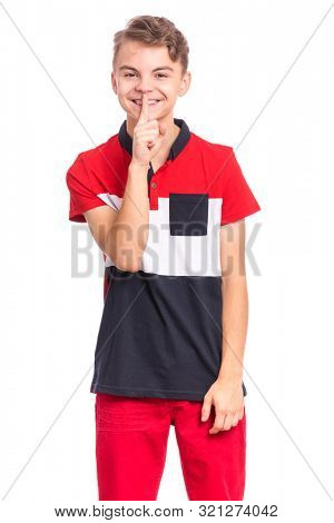 Teen boy asking to be quiet with finger on lips, isolated on white background. Cute young teenager making keep Quiet gesture. Child asking for silence or secrecy with finger on lips shh sign symbol.