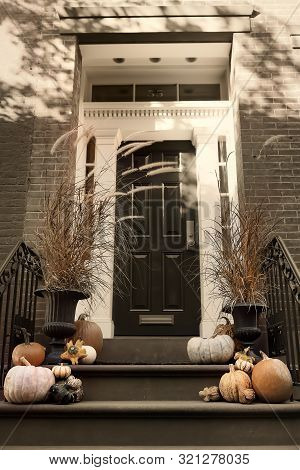 Toned Retro Style Photo Of Typical Of A Front Door And Porch Decorated With Pumpkins For Halloween O