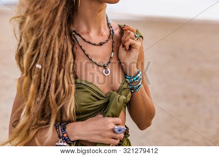 Close Up Of Beautiful Young Stylish Woman Walking On The Beach At Sunset