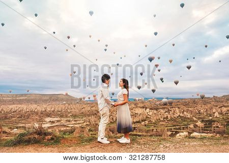 Asian Couple Watching Colorful Hot Air Balloons Flying Over The Valley At Cappadocia, Turkey This Ro