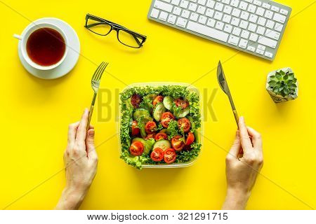 Healthy Dinner In Lunch Box And Hands With Flatware Near Keyboard And Tea On Yellow Background Top V