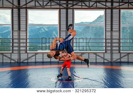A  Wrestler Boy In A Sports Tights Wrestles With An Adult Male Wrestler On A Wrestling Carpet In The